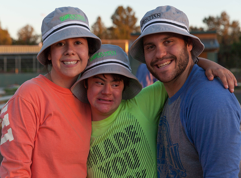 A group of three smile while wearing Camp Civitan hats.