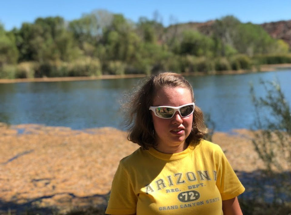 A woman wearing white sunglasses smiles before a lake.