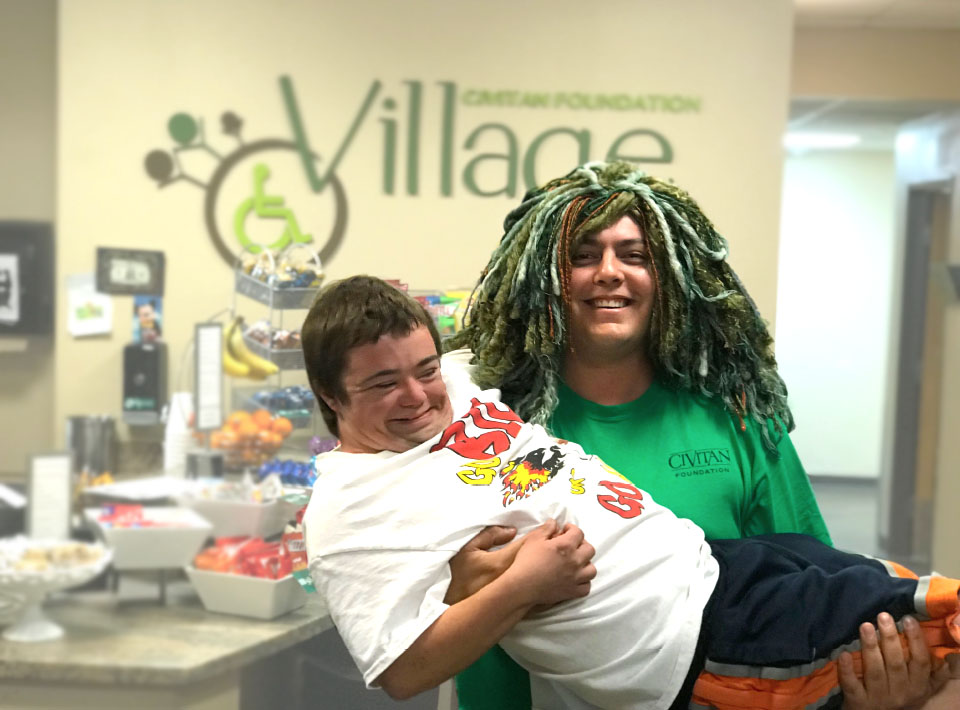 Two friends smiling, one holding the other and wearing a green hair wig